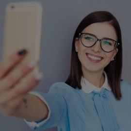 Smiling businesswoman making selfie photo on smartphone. Wearing in blue shirt and glasses. Standing over gray background